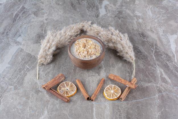 Een houten kom gezonde cornflakes met melk en kaneelstokjes.