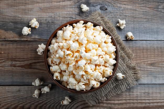Een houten kom gezouten popcorn.