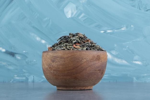 Een houten kom met gedroogde theeblaadjes.