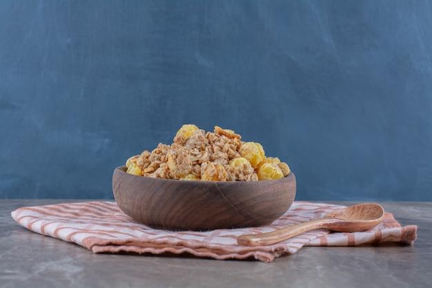 Een houten kom met gezonde cornflakes en een lege houten lepel.