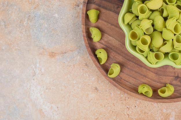 Een houten kom met groen bord groene onbereide macaroni.