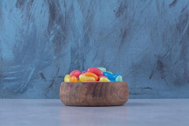 Een houten kom met kleurrijke zoete jelly bean snoepjes.