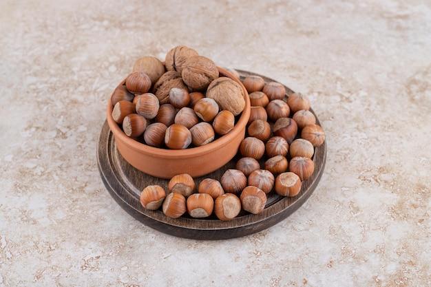 Een houten kom met macadamia noten en walnoten