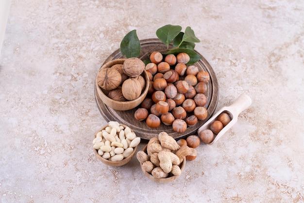 Een houten kom met macadamianoten en walnoten.