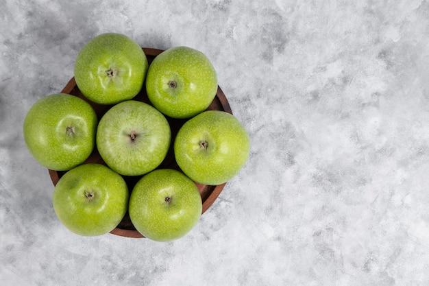 Een houten kom met verse groene zoete appels op steen