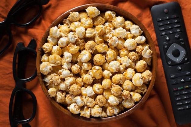 Een houten kom popcorn en afstandsbediening.