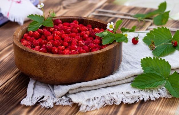 Een houten kom rode rijpe wilde aardbeien en bloemen op een oude houten ondergrond.