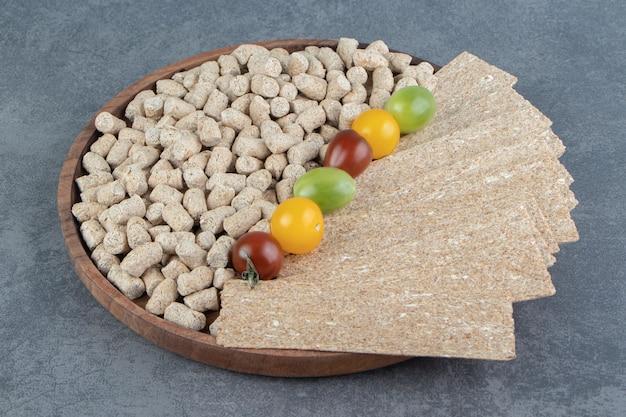 Een houten kom rogge krokante granen met kleurrijke tomaten.