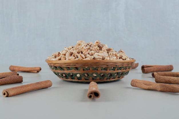 Een houten kom vol gezonde granen met kaneelstokjes.