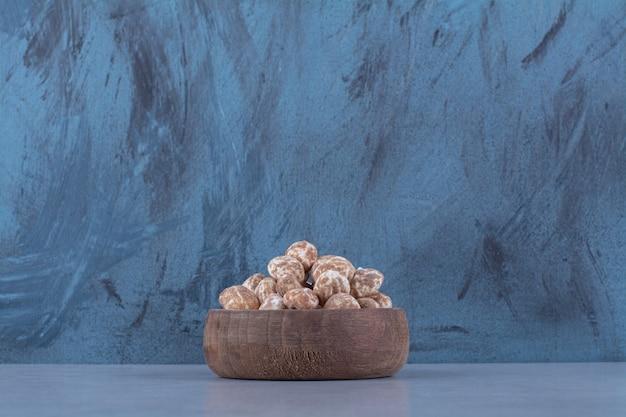 Een houten kom vol gezonde granen op een grijze ondergrond
