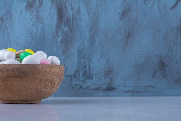 Een houten kom vol kleurrijke bonensnoepjes op grijs oppervlak