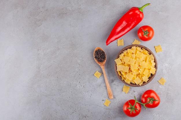 Een houten kom vol met ongekookte ravioli pasta met rode verse tomaten en chili peper.