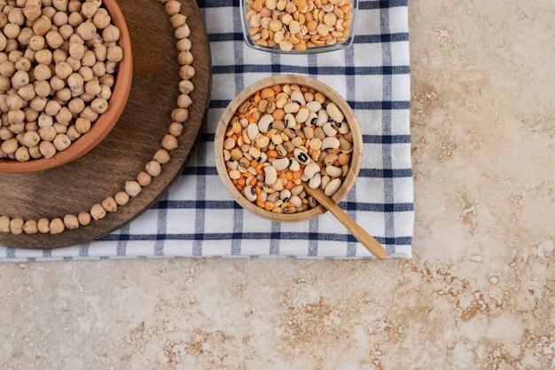 Een houten kom vol onbereide erwten met kruiden en bonen.