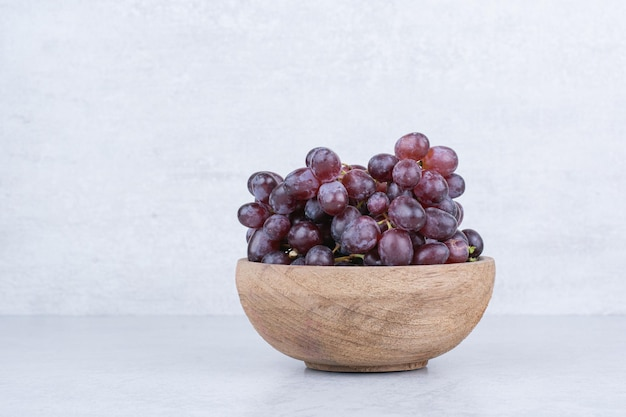 Een houten kom vol paarse druiven op wit
