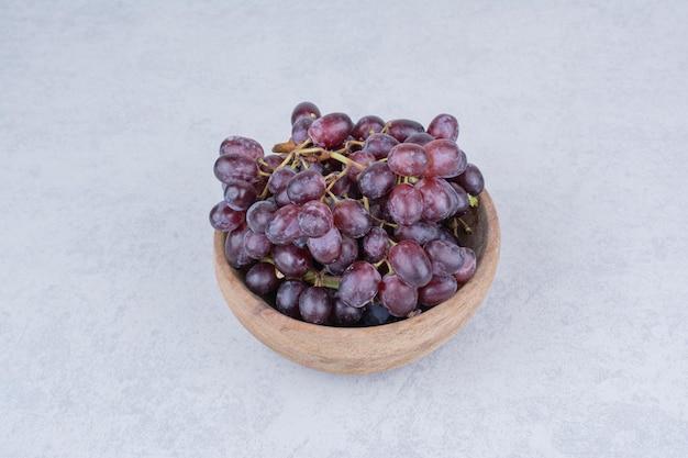 Een houten kom vol paarse druiven op witte achtergrond. hoge kwaliteit foto Gratis Foto