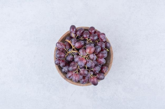 Een houten kom vol paarse druiven op witte achtergrond. hoge kwaliteit foto