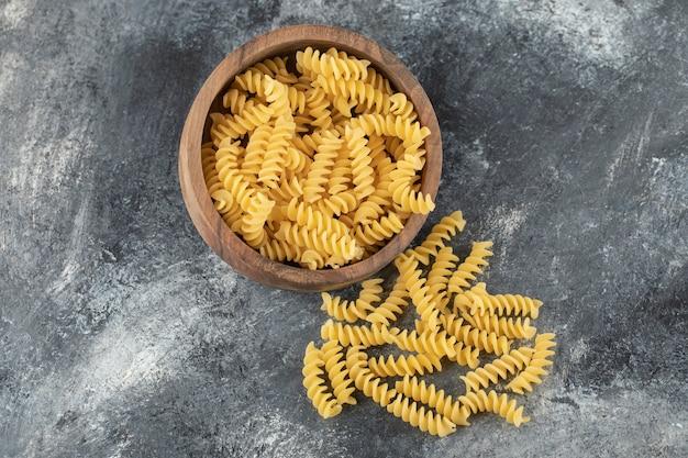 Een houten kom vol rauwe droge fusilli-pasta.