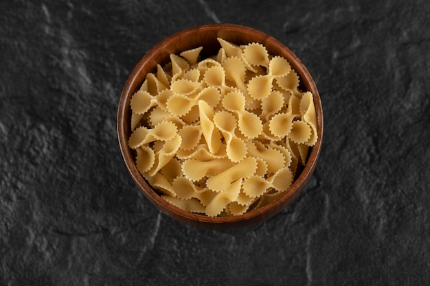 Een houten kom vol rauwe farfalle tonde macaroni.
