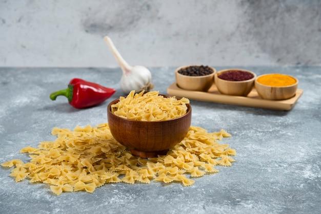 Een houten kom vol rauwe macaroni en kruiden.