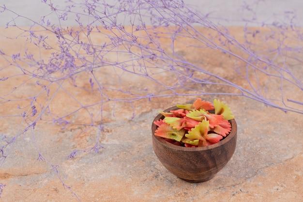 Een houten kom vol vlinderdasdeegwaren op marmeren achtergrond. hoge kwaliteit foto