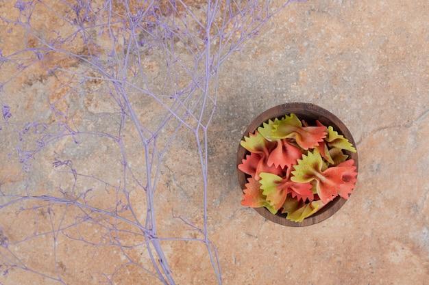 Een houten kom vol vlinderdaspasta op marmeren ruimte.