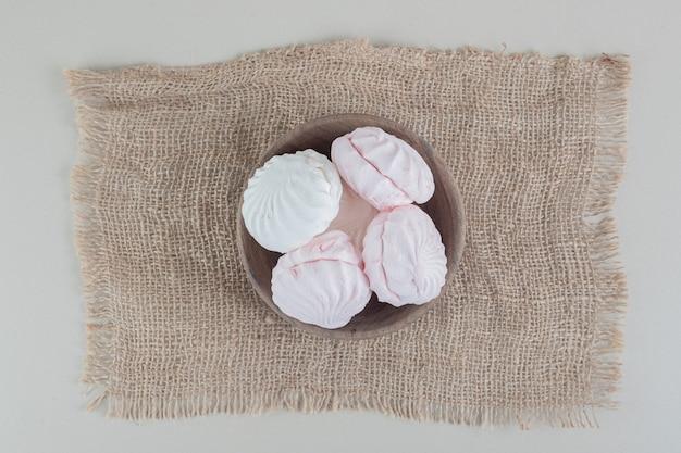 Een houten kom vol witte en roze zephyrs.