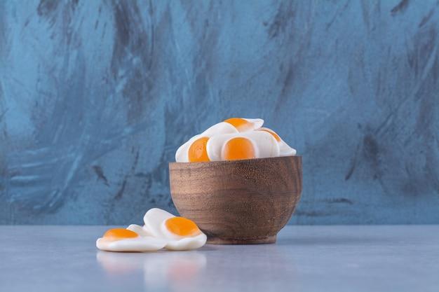 Een houten kom vol zoete gelei-gebakken eieren op grijze tafel.