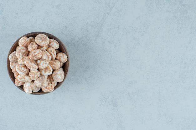 Een houten kom vol zoete heerlijke peperkoek op witte ondergrond