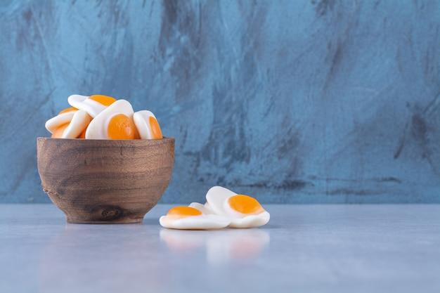 Een houten kom vol zoete, in gelei gebakken eieren op een grijze ondergrond
