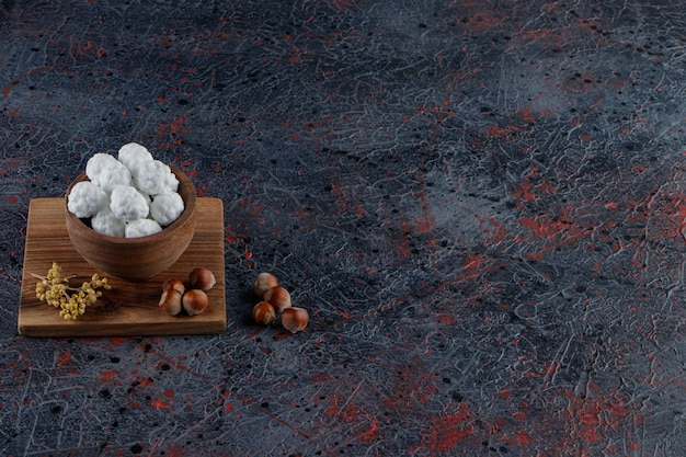 Een houten kom vol zoete witte snoepjes met gezonde noten op een donkere tafel.