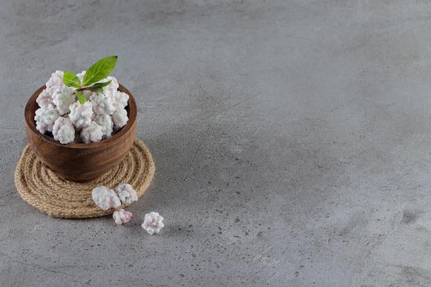 Een houten kom vol zoete witte snoepjes met muntblaadjes op een steen