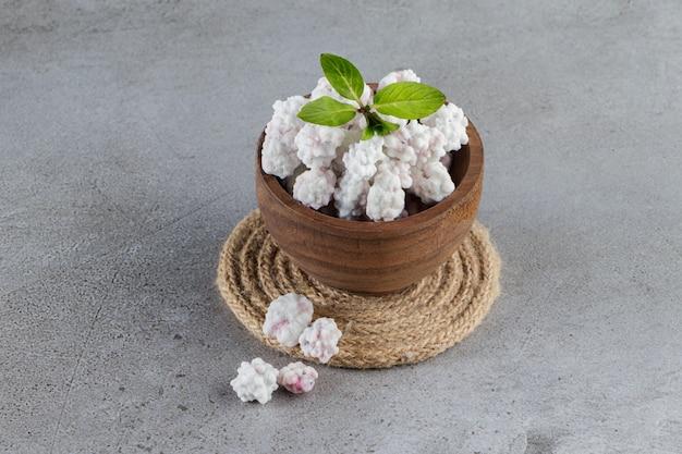 Een houten kom vol zoete witte snoepjes met muntblaadjes op een stenen ondergrond