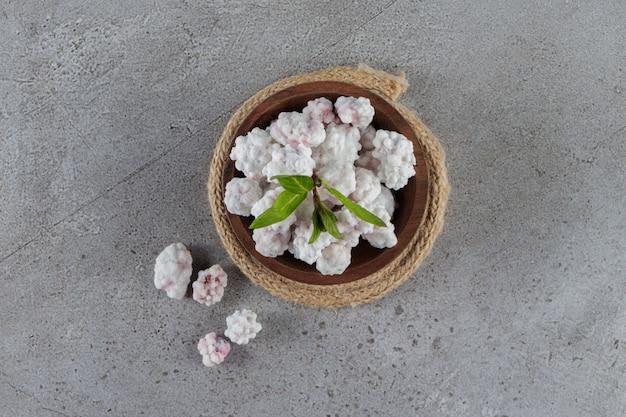 Een houten kom vol zoete witte snoepjes met muntblaadjes op een stenen tafel.
