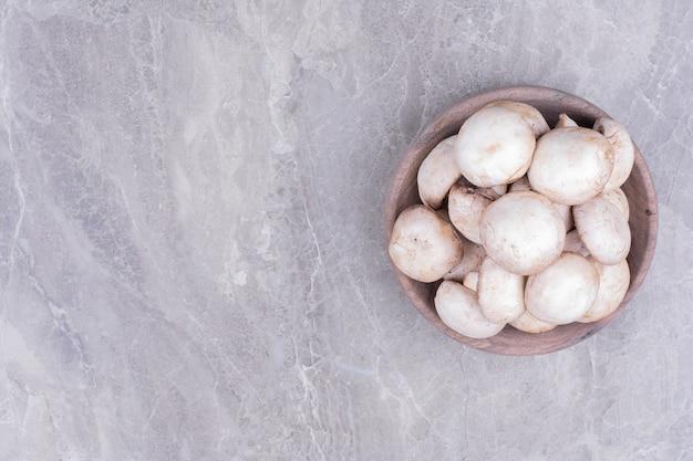 Een houten kopje champignons op het marmer