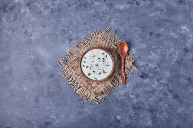 Een houten kopje yoghurtsoep met kruiden.