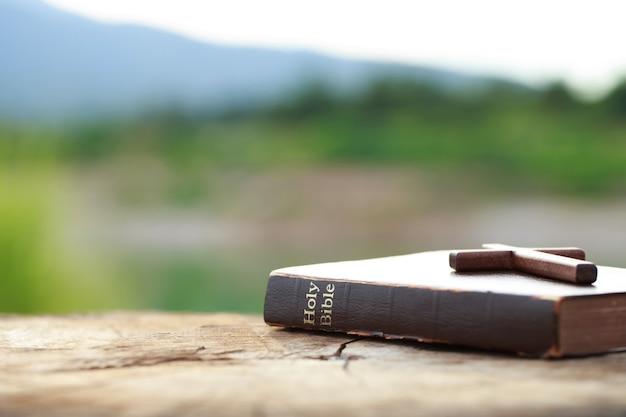 Een houten kruis op de heilige bijbel op houten tafel zondagslezingen bijbelonderwijs