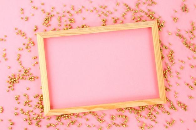 Een houten leeg frame op een pastel achtergrond omgeven door glanzende decoratieve sterren en ballen.