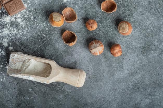 Een houten lepel met macadamia noten op grijs.