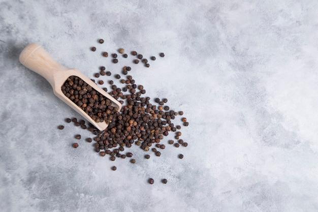 Een houten lepel vol zwarte peperkorrels die op stenen tafel worden geplaatst. hoge kwaliteit foto