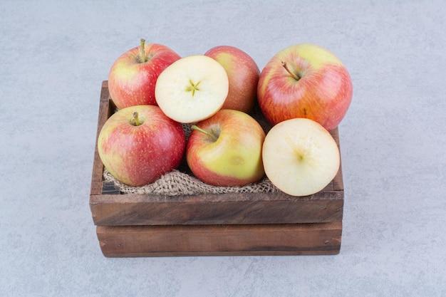 Een houten mand vol appels op wit