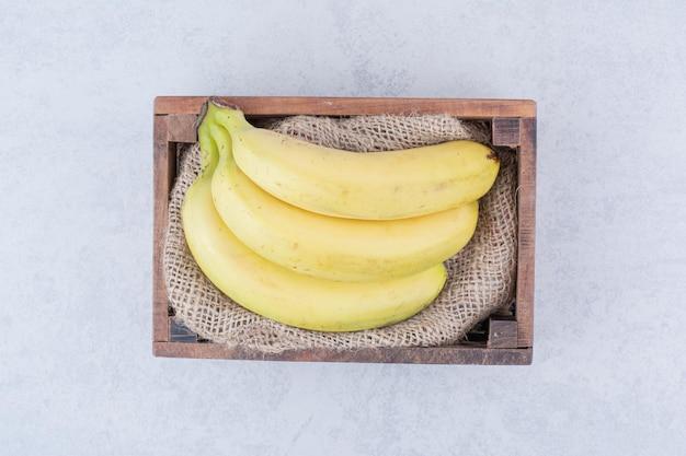 Een houten mand vol rijpe fruitbananen op witte achtergrond. hoge kwaliteit foto