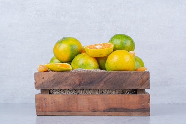 Een houten mand vol zure mandarijn op wit