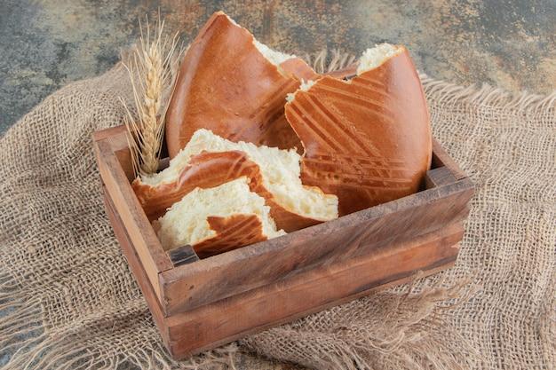 Een houten mandje met heerlijk zoet gebak op een zak