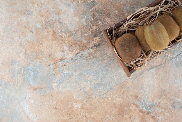 Een houten mandje met verse kiwi op marmeren tafel.