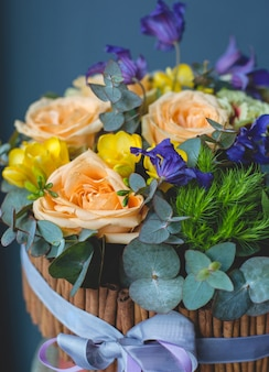 Een houten mandje met zoete kleurrozen voor een geschenk.