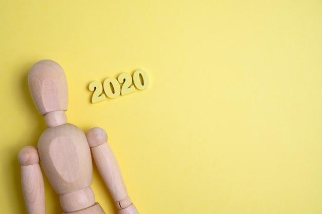 Een houten mannequin naast de cijfersachtergrond van 2020