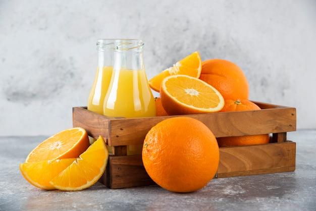 Een houten oude doos vol met oranje fruit en glazen kruiken sap op stenen tafel.