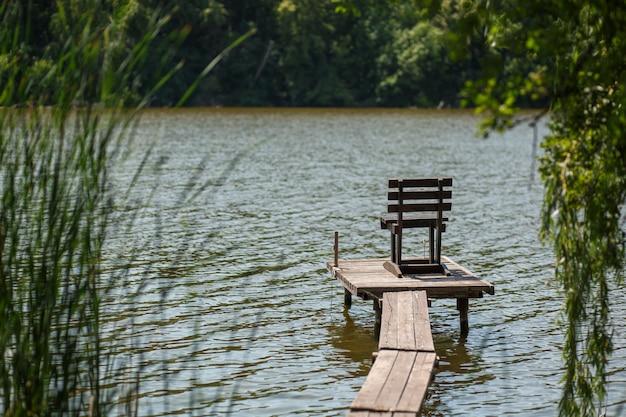 Een houten pier op een meer met een vissersstoel
