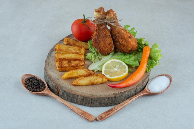 Een houten plaat met gebakken cgicken en groenten op marmeren tafel.