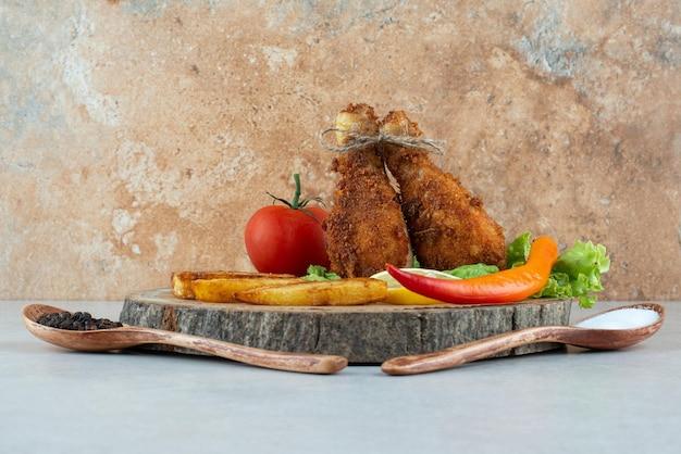 Een houten plaat met gebakken kip en groenten op marmer